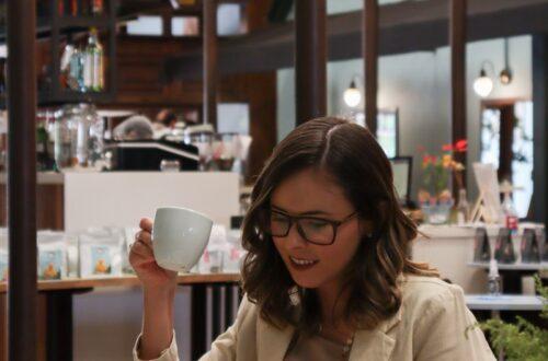 woman in white coat holding white ceramic mug